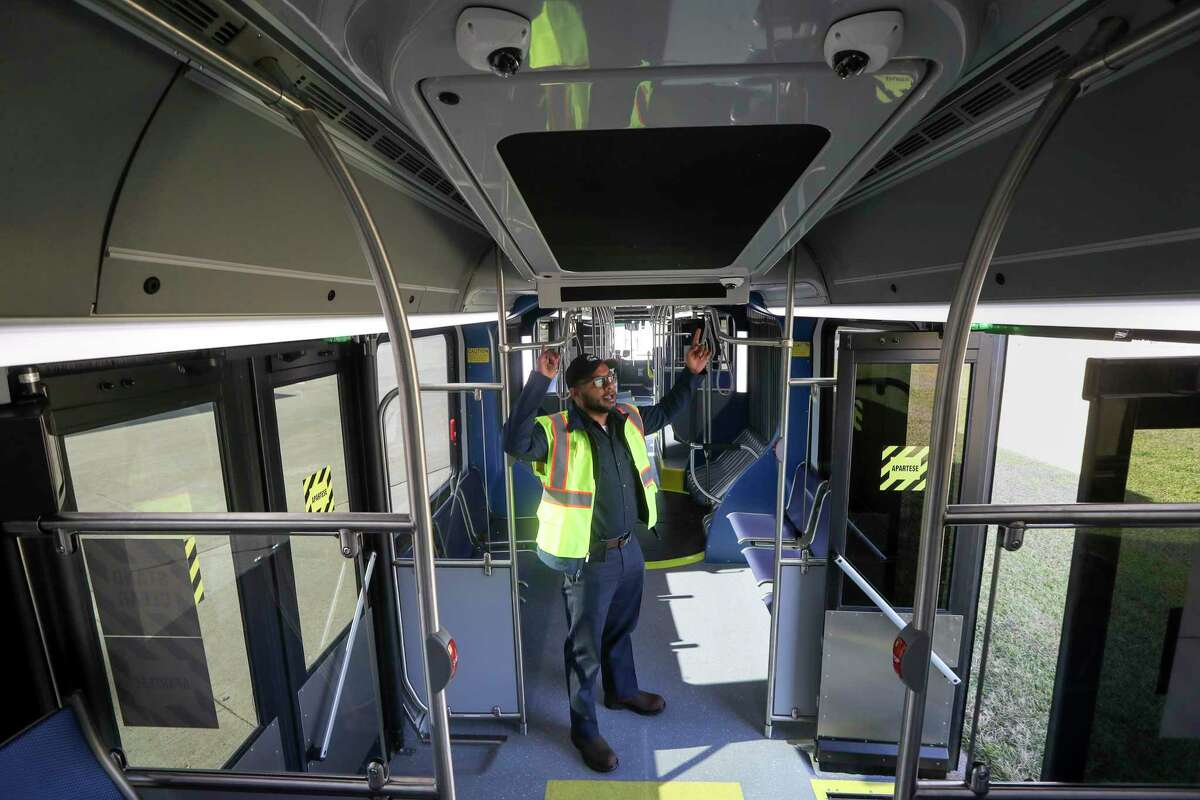Kevin Abraham, a mechanic with Metropolitan Transit Authority, gives a tour of one of the new 60-foot buses that will operate Uptown bus rapid transit line, on Nov. 25, 2019, in Houston.