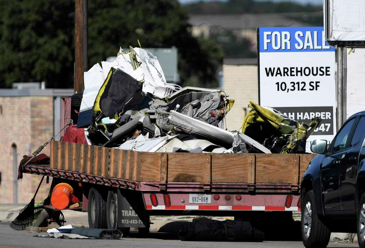 The remains of a Piper Comanche that crashed in the 600 block of West Rhapsody on Sunday night rest on a trailer at the site on Tuesday. Three people were killed in the crash.
