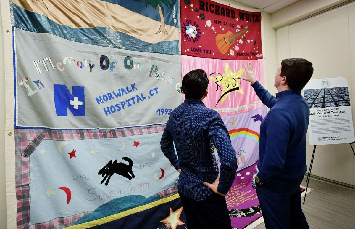 Visitors to the Circle Care Center including Rene Soto and Sean-Michael Hazuda, Executive Director of the Triangle Community Center, view a section of the AIDS Memorial Quilt in recognition of World Aids Day 2019, Tuesday, December 3, 2019, at the Center in Norwalk, Conn. The Center will be hosting the display from December 4 through December 20 at their location, 618 West Avenue. The AIDS Memorial Quilt was created in 1987 as a memorial to those who have died of AIDS and as a way of helping others to understand the impact of the disease. The quilt is made up of panels that commemorate the life of someone who has died of AIDS.
