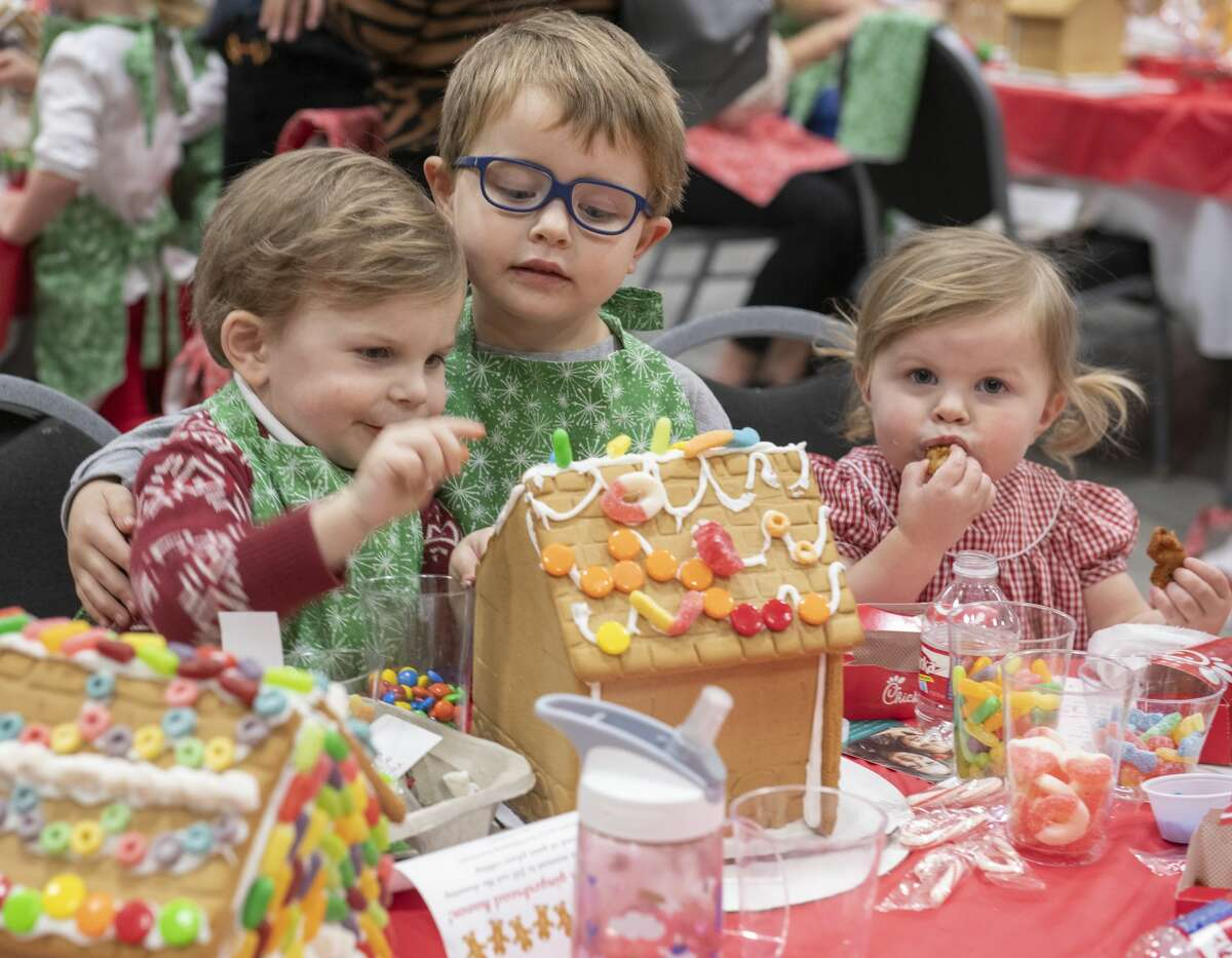Scenes from Gingerbread Haven benefiting Midland Fair Havens: Thomas, 2, Mason, 4 and Mary Collins Midkiff, 1, take turns decorating their gingerbread house and eating the decorations 12/03/19 at the annual Gingerbread Haven benefiting Midland Fair Havens. Tim Fischer/Reporter-Telegram