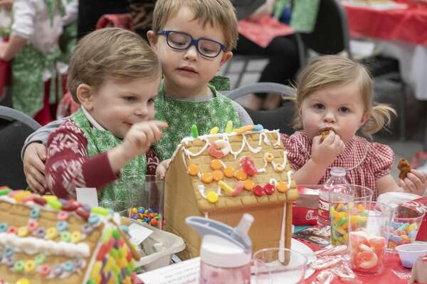 Thomas, 2, Mason, 4 and Mary Collins Midkiff, 1, take turns decorating their gingerbread house and eating the decorations 12/03/19 at the annual Gingerbread Haven benefiting Midland Fair Havens. Tim Fischer/Reporter-Telegram