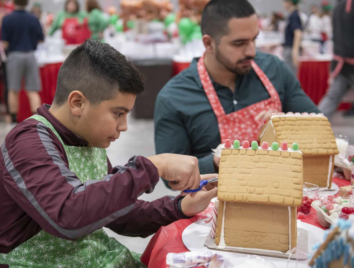 Blaise Sanchez cuts candy ribbon for his gingerbread house as Emilio Castellon works on decorating his gingerbread house 12/03/19 at the annual Gingerbread Haven benefiting Midland Fair Havens. Tim Fischer/Reporter-Telegram