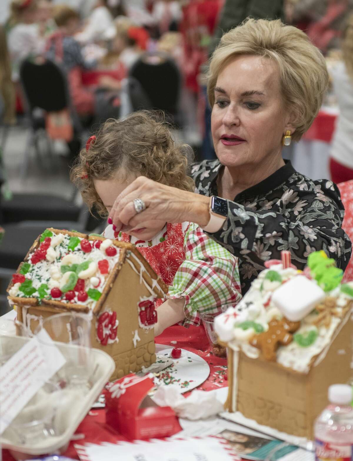 Emily Blonkvist gets help from her granddaughter Annie as they work on decorating their gingerbread house 12/03/19 at the annual Gingerbread Haven benefiting Midland Fair Havens. Tim Fischer/Reporter-Telegram