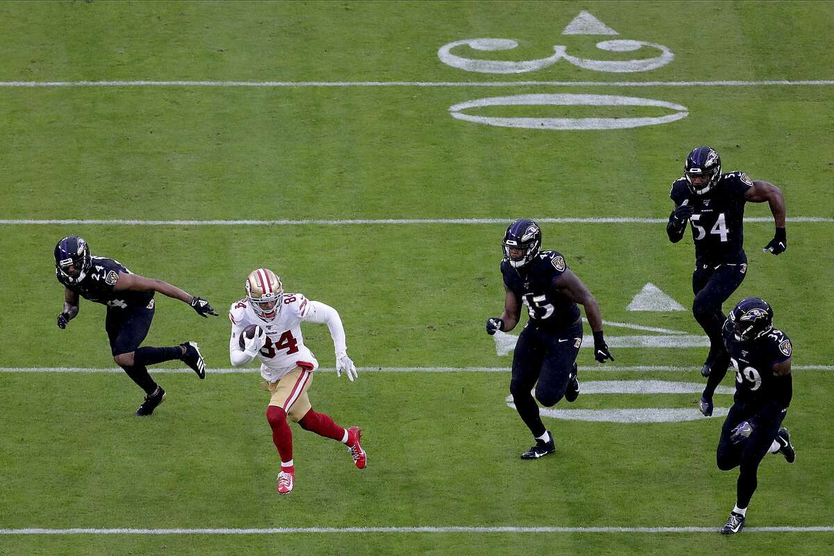 San Francisco 49ers wide receiver Kendrick Bourne (84) runs with the ball as a host of Baltimore Ravens defenders chase him during the first half of NFL football game, Sunday, Dec. 1, 2019, in Baltimore. The Ravens won 20-17. (AP Photo/Julio Cortez)