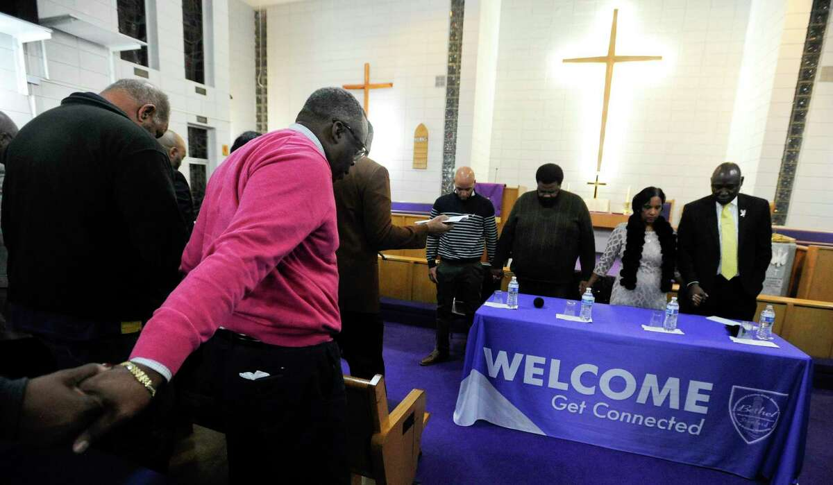 Attendees join in prayer, along with attorney Benjamin Crump, at right, holding hands Valerie Jaddo and Steven Barrier Sr. at the start of a Community Rally for Justice at Bethel A.M.E. Church in Stamford on Tuesday.