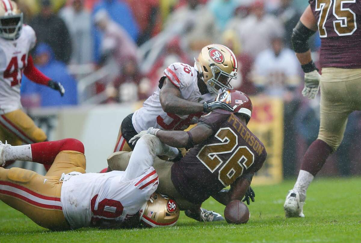 LANDOVER, MD - OCTOBER 20: Sheldon Day #96 and Kwon Alexander #56 of the San Francisco 49ers tackle Adrian Peterson #26 of the Washington Redskins, forcing a fumble, during the game at FedExField on October 20, 2019 in Landover, Maryland. The 49ers defeat