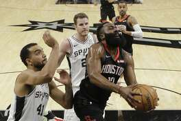 Houston Rockets guard James Harden (13) drives past San Antonio Spurs forward Trey Lyles (41) and center Jakob Poeltl (25) during the first half of an NBA basketball game in San Antonio, Tuesday, Dec. 3, 2019. (AP Photo/Eric Gay)