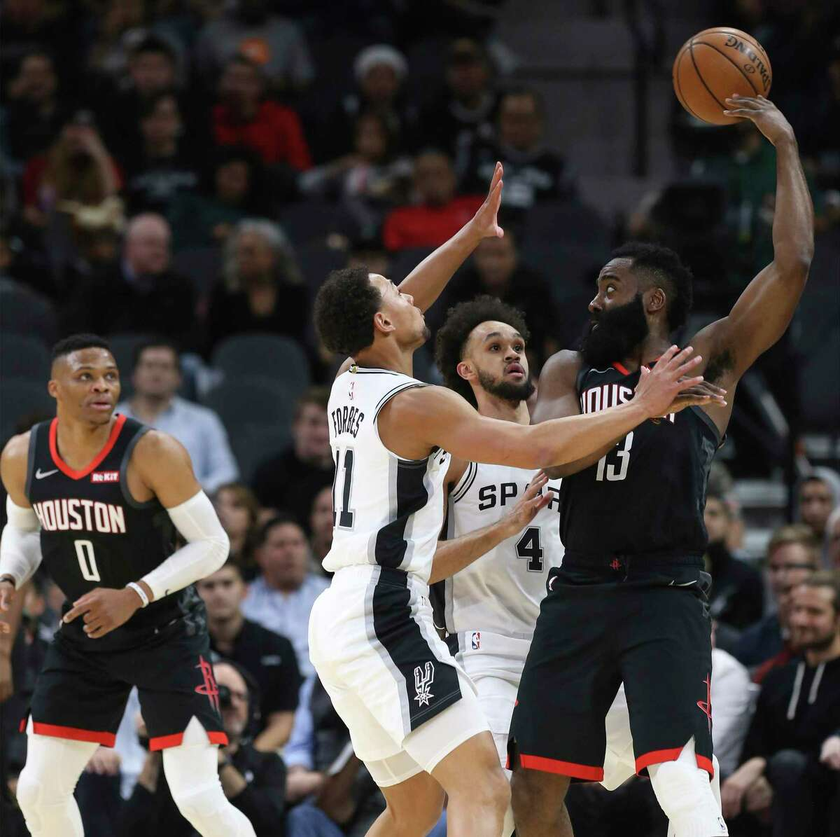 Houston Rockets' James Harden (13) flips the ball to teammate Russell Westbrook (00) while defended by Spurs' Bryn Forbes (11) and Derrick White (04) during their game at the AT&T Center on Tuesday, Dec. 3, 2019.