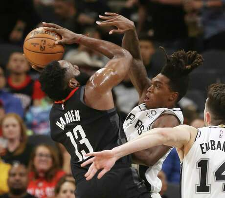 Spurs' Lonnie Walker IV (01) puts pressure on Houston Rockets' James Harden (13) during their game at the AT&T Center on Tuesday, Dec. 3, 2019.