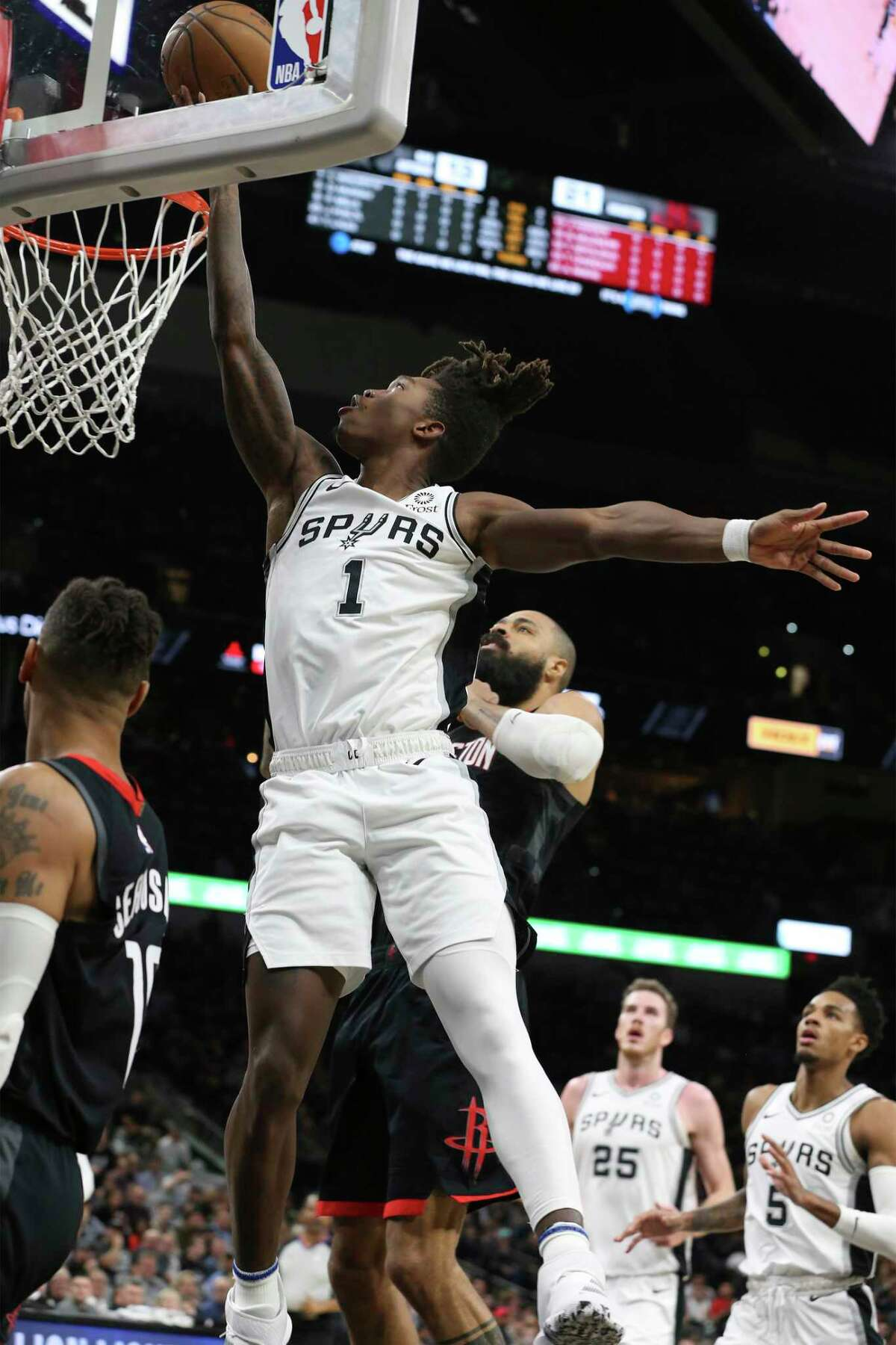 Spurs' Lonnie Walker IV (01) goes in for a score against Houston Rockets' Tyson Chandler (19) and Thabo Sefolosha (18) during their game at the AT&T Center on Tuesday, Dec. 3, 2019.