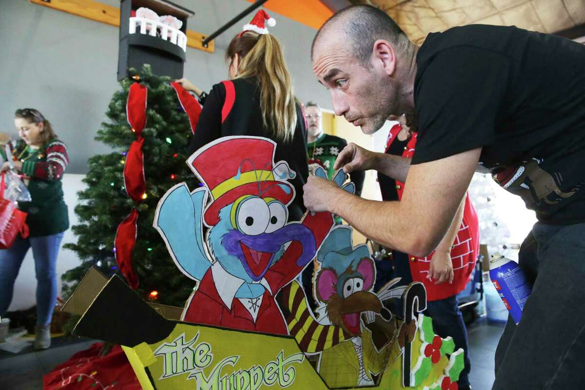 Jose Crespo works on the Marshall's display as local businesses decorate Christmas trees at the Children's Shelter campus on Dec. 3, 2019.