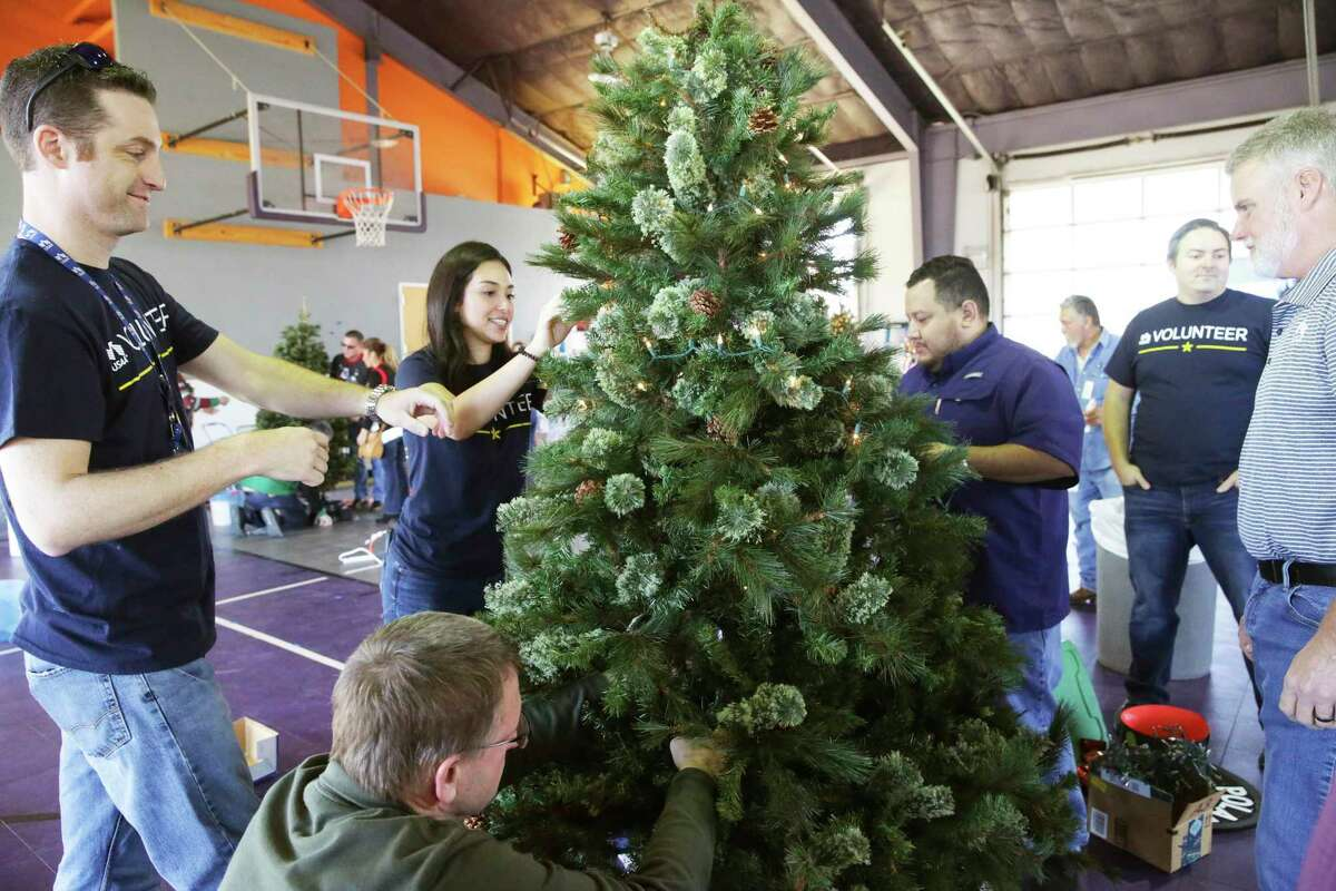 The USAA team converges to set up their entry as local businesses decorate Christmas trees at the Children's Shelter campus on Dec. 3, 2019.