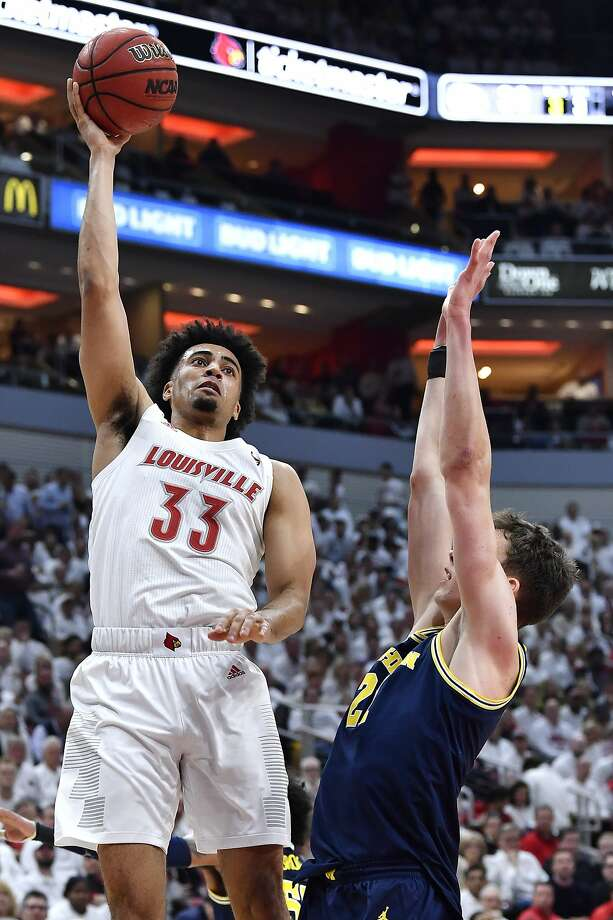 Louisville forward Jordan Nwora shoots over the outstretched arms of Michigan guard Franz Wagner during the second half. Photo: Timothy D. Easley / Associated Press