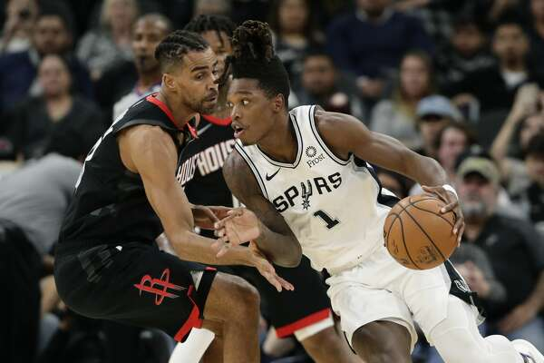 San Antonio Spurs guard Lonnie Walker IV (1) drives around Houston Rockets forward Thabo Sefolosha during the first half of an NBA basketball game in San Antonio, Tuesday, Dec. 3, 2019. (AP Photo/Eric Gay)