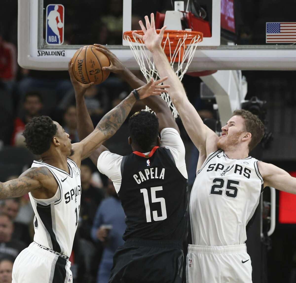 Spurs' DeMar DeRozan (10) and Jakob Poeltl (25) defend against Houston Rockets' Clint Capela (15) during their game at the AT&T Center on Tuesday, Dec. 3, 2019.
