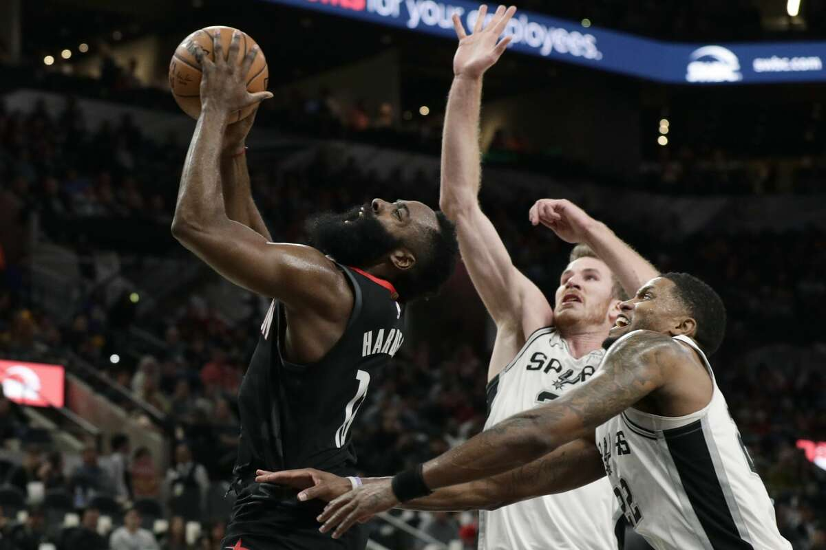 Houston Rockets guard James Harden (13) drives past San Antonio Spurs forward Rudy Gay, right, and center Jakob Poeltl during the first half of an NBA basketball game in San Antonio, Tuesday, Dec. 3, 2019. (AP Photo/Eric Gay)