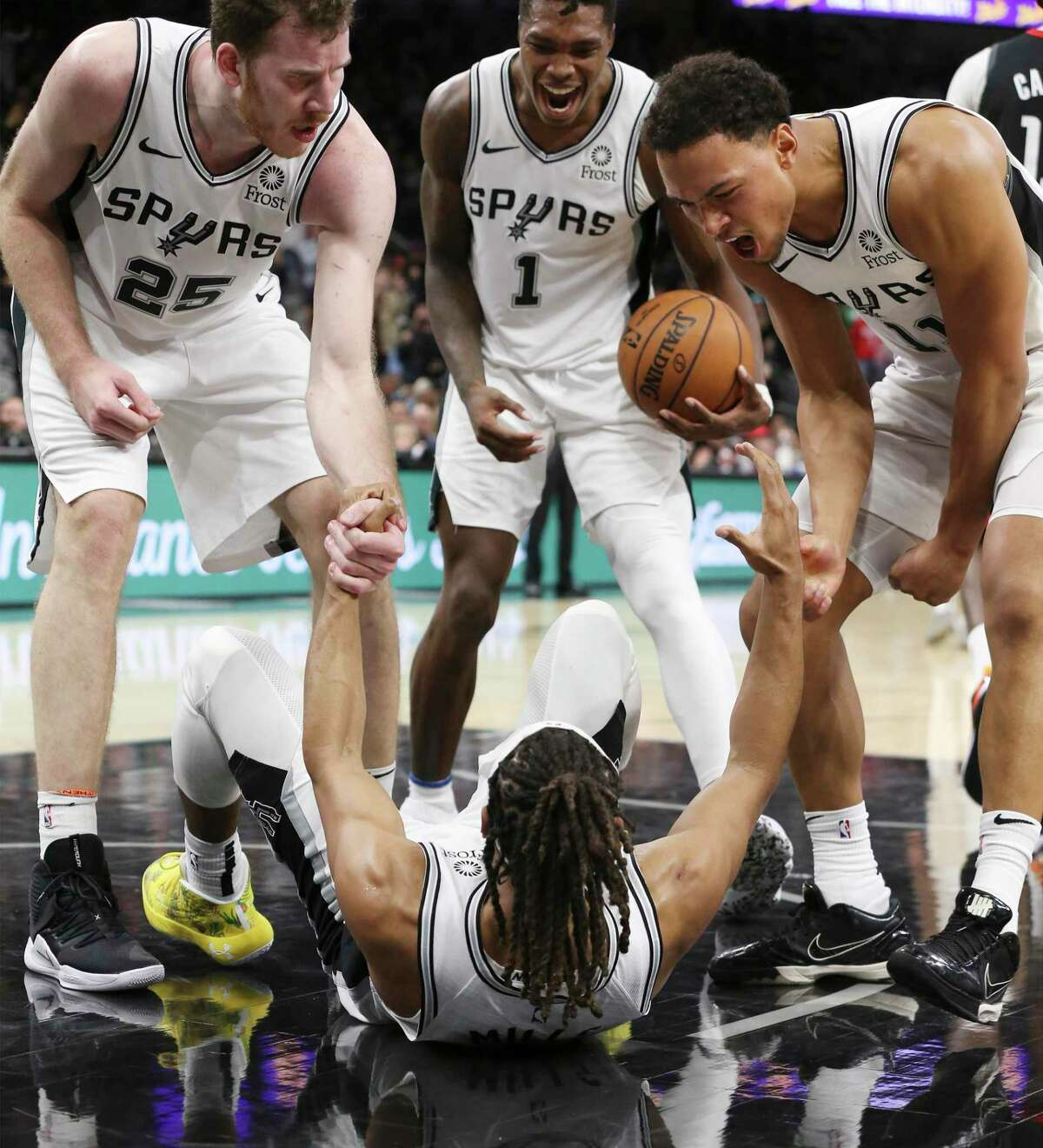 Jakob Poeltl, from left, Lonnie Walker IV and Bryn Forbes get fired up after Patty Mills drew a charge on Houston's Clint Capela in Tuesday's second overtime.