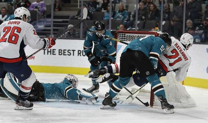 Washington Capitals' Garnet Hathaway, right, scores a goal past San Jose Sharks' Radim Simek (51) during the second period of an NHL hockey game Tuesday, Dec. 3, 2019, in San Jose, Calif. (AP Photo/Ben Margot)