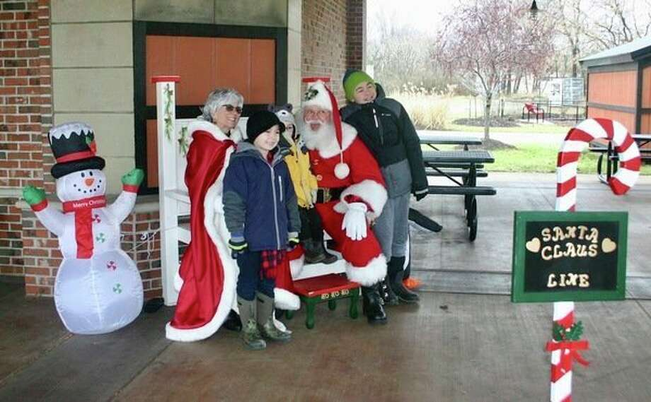 Visitors to the Reed City Depot were greeted by Santa and Mrs. Claus on Saturday, Nov. 30 during the annual Evergreen Festival. Children took photos with Santa and decorated holiday cookies. (Herald Review photo/Cathie Crew)