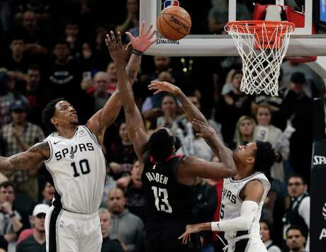 The Spurs' DeMar DeRozan (10) and Dejounte Murray deny Rockets guard James Harden (13) a bucket in the second overtime of San Antonio's 135-133 victory Tuesday night.