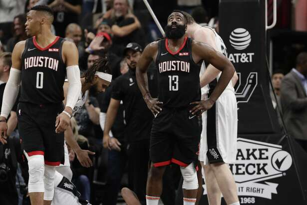 Houston Rockets guard Russell Westbrook (0) and guard James Harden (13) react to a play during overtime of an NBA basketball game against the San Antonio Spurs, in San Antonio, Tuesday, Dec. 3, 2019. San Antonio won 135-133 in double overtime. (AP Photo/Eric Gay)