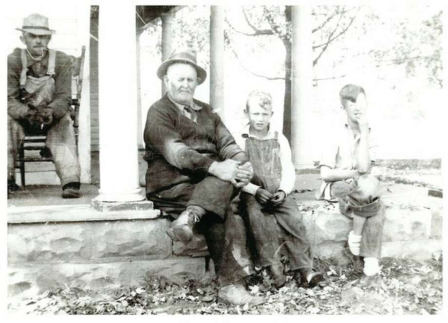 This is a three generation photo with Cecil Fillmore in the background and his dad, Fred Fillmore, sitting beside his grandsons, Tom and Dewitt. All three grandsons grew up in Fred Fillmore's house.