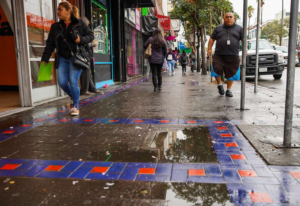 People walk on Mission Street after heavy rains in San Francisco, California, on Monday, Dec. 2, 2019.