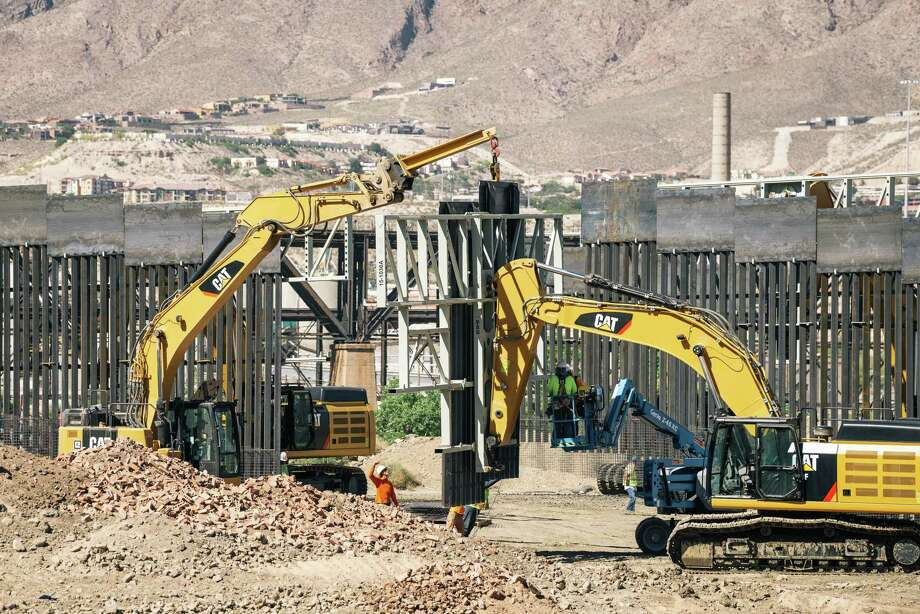 Fisher Industries workers drop pieces of wall into place on May 24, 2019, on land owned by American Eagle Brick Co. in Sunland Park, N.M., near the U.S.-Mexico border. The project was pursued by a right-wing group, We Build the Wall, which is also trying to erect steel fencing along the banks of the Rio Grande in Texas. Photo: Photo For The Washington Post By Jordyn Rozensky And Justin Hamel / Jordyn Rozensky and Justin Hamel