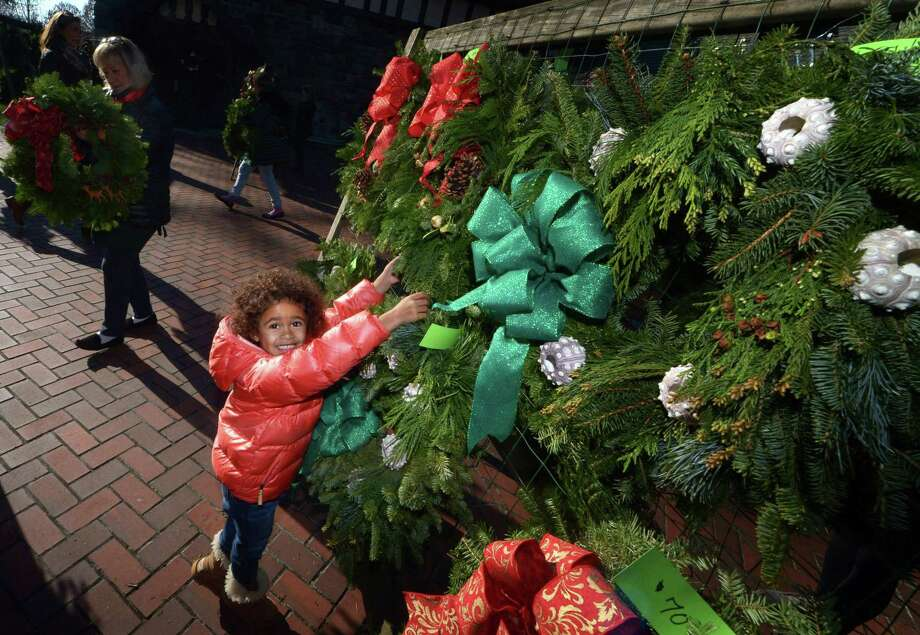 Three-year-old Emerson Edwards helps her mom pick out a wreath duringThe Rowayton Gardeners' Annual Christmas Market Saturday, December 1, 2018 at the Rowayton Community Center in Norwalk, Conn. The Christmas Market which featured over a hundred decorated wreaths is their largest fundraiser and its profits help provide garden-inspired classes, workshops and lectures for all ages, raise community awareness about the environment and maintain our town's lovely public gardens. Photo: Erik Trautmann / Hearst Connecticut Media / Norwalk Hour