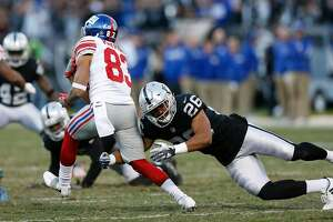OAKLAND, CA - DECEMBER 03: Kalif Raymond #83 of the New York Giants is tackled by Shalom Luani #26 of the Oakland Raiders at Oakland-Alameda County Coliseum on December 3, 2017 in Oakland, California. (Photo by Lachlan Cunningham/Getty Images)