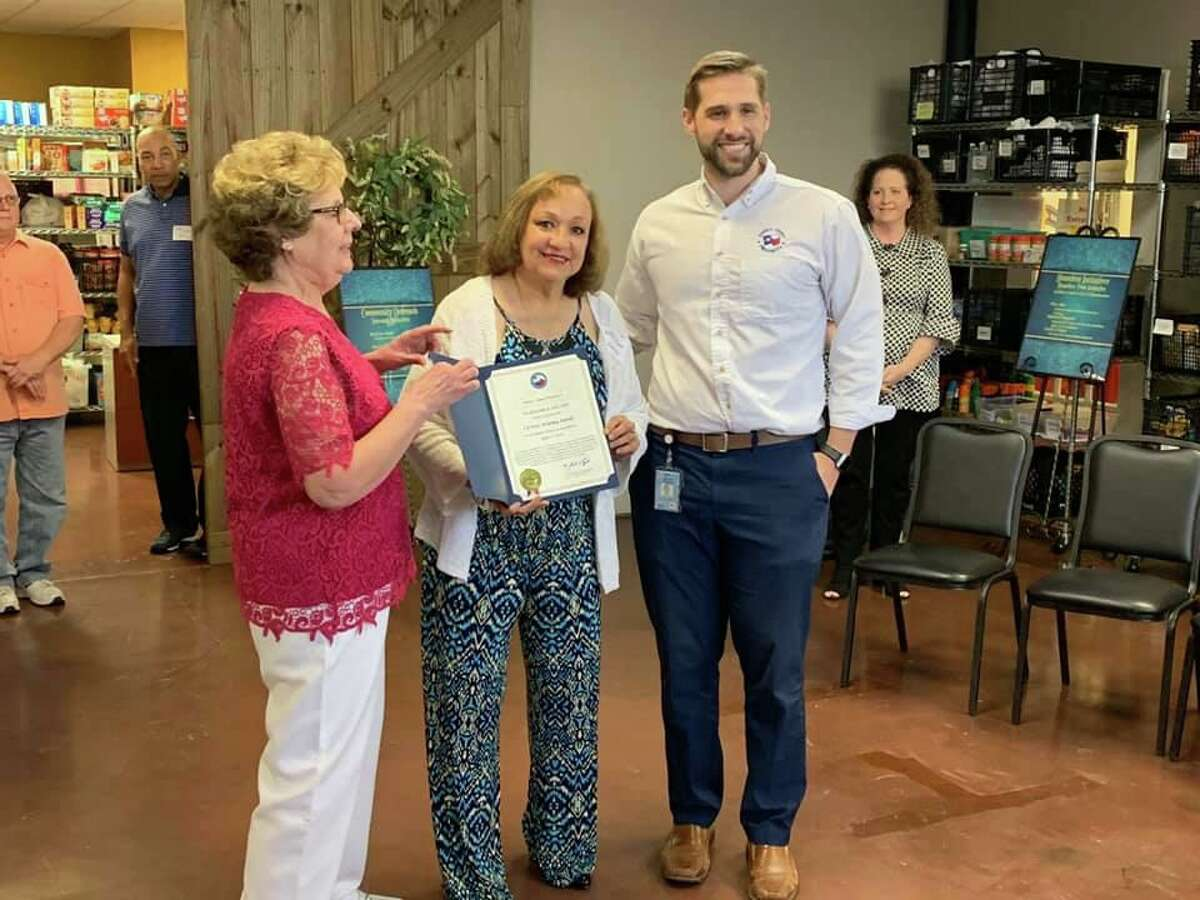 Jean Dreyer and Patricia Hudson celebrate a ribbon cutting for the new location of Cy-Fair Helping Hands, a nonprofit aiding the homeless, with Harris County Precinct 4 community aide Cody Holder.
