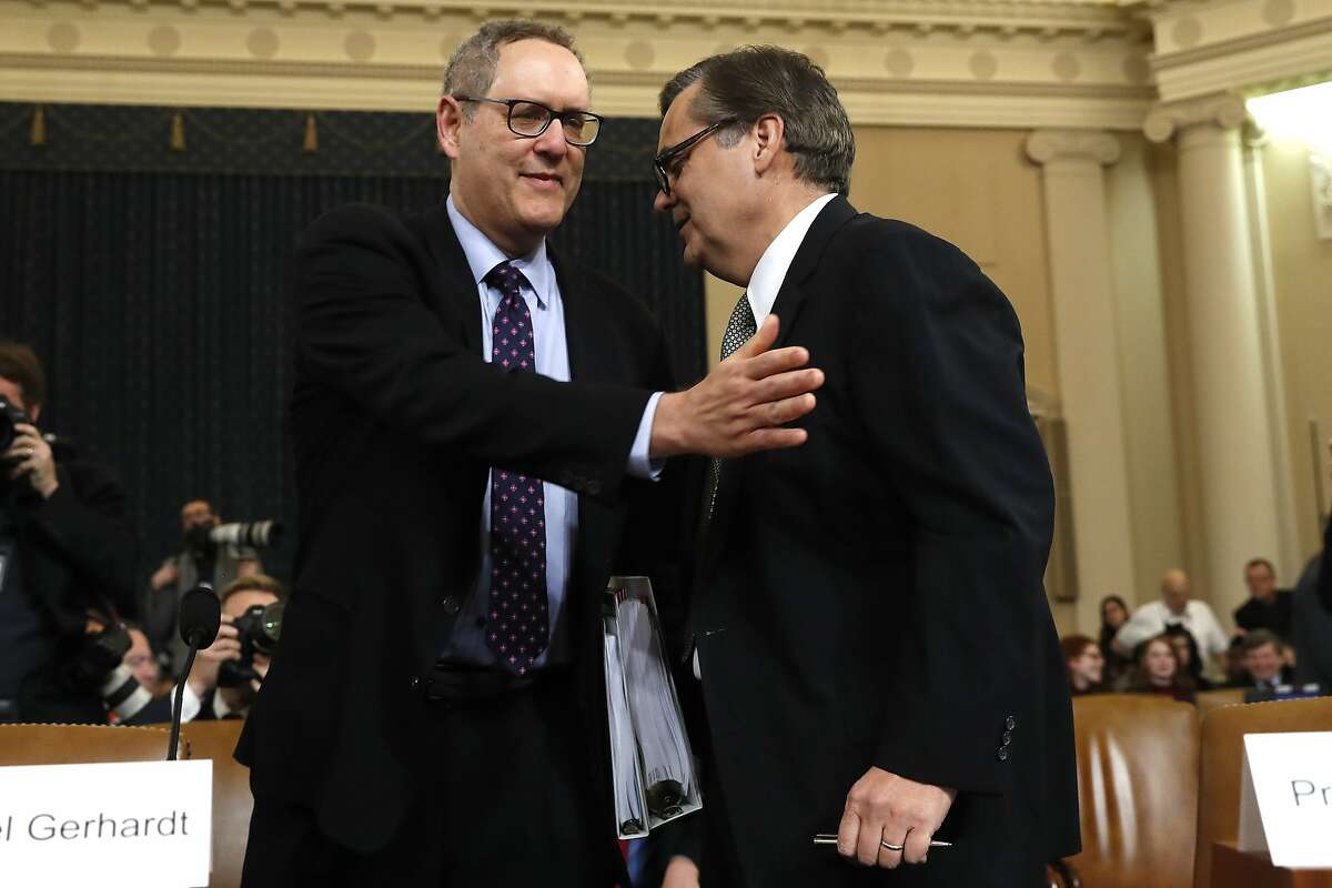 Constitutional law experts University of North Carolina Law School professor Michael Gerhardt, left, and George Washington University Law School professor Jonathan Turley, talks as they arrive to testify during a hearing before the House Judiciary Committee on the constitutional grounds for the impeachment of President Donald Trump, Wednesday, Dec. 4, 2019, on Capitol Hill in Washington. (AP Photo/Jacquelyn Martin)