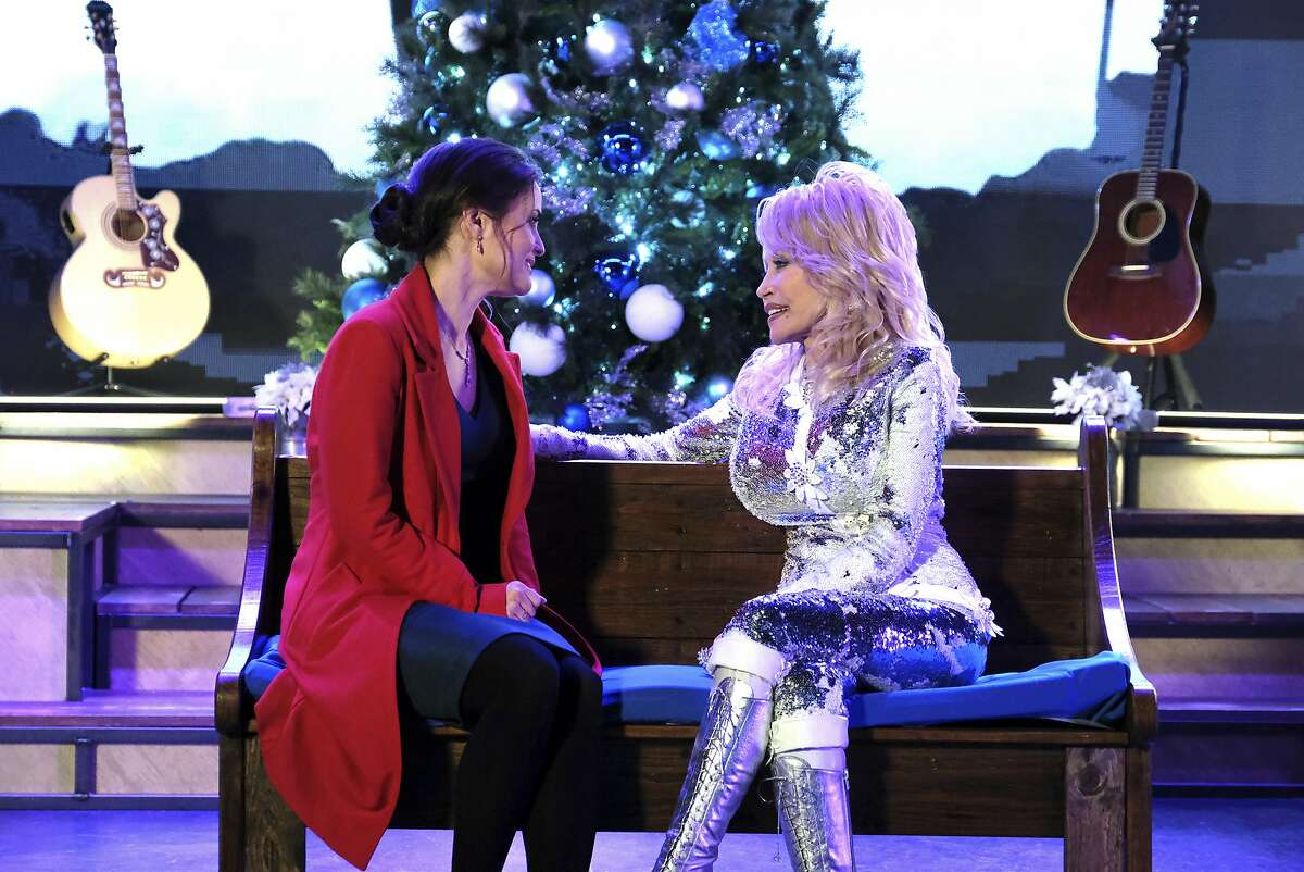 This image released by Crown Media United States LLC shows Danica McKellar, left, and Dolly Parton in a scene from