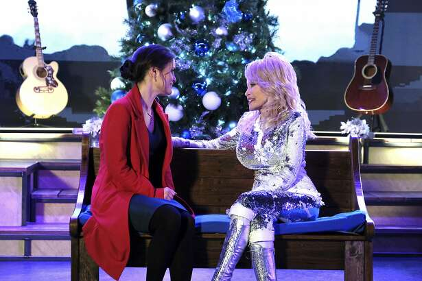 """This image released by Crown Media United States LLC shows Danica McKellar, left, and Dolly Parton in a scene from """"Christmas at Dollywood,"""" airing Dec. 8 on the Hallmark Channel. (Curtis Hilbun/Crown Media United States LLC via AP)"""