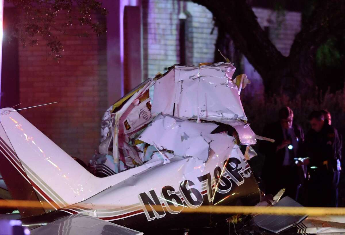 A wrecked Piper Comanche airplane rests on the 600 block of Rhapsody after it crashed, killing three people, on approach to San Antonio International Airport on Sunday night.