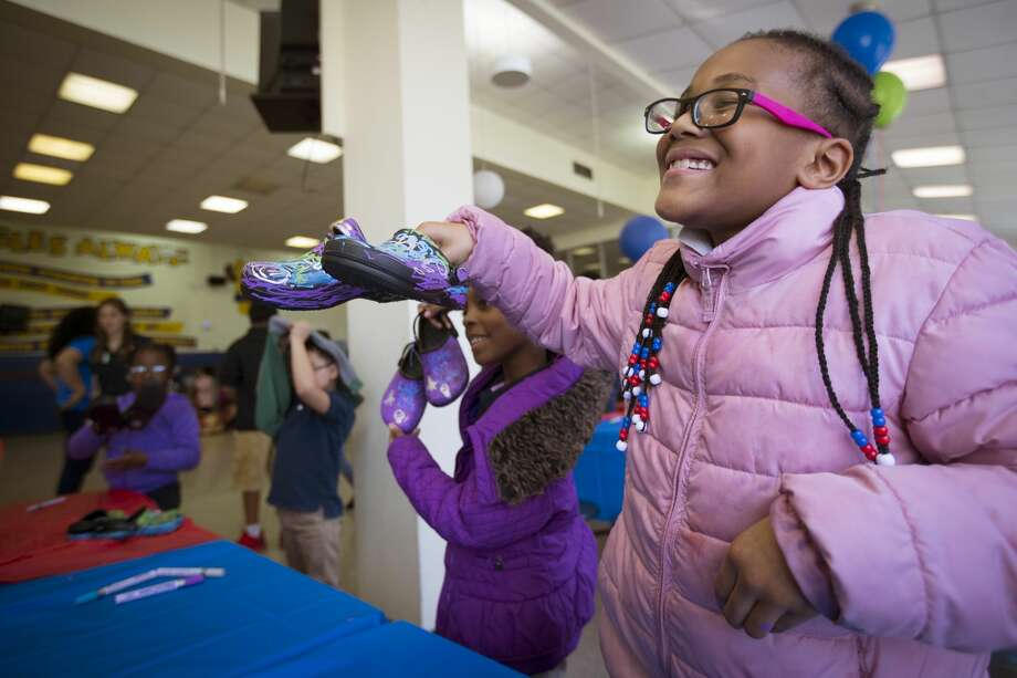 Wesley Elementary student Amuarie Burke shows off her new shoes after she decorated them in the school's cafeteria on Tuesday, Dec. 3, 2019, in Houston. Hundreds of children received brand new shoes this Giving Tuesday, thanks to local nonprofit Communities In Schools of Houston. CIS is partnering with Skechers, the department store Gordmans, and the national nonprofit Soles4Souls to provide more than 4,000 donated pairs of new shoes. Photo: Brett Coomer/Staff Photographer