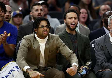 SAN FRANCISCO, CALIFORNIA - NOVEMBER 25:  Injured players D'Angelo Russell #0 (left) and Stephen Curry #30 of the Golden State Warriors react on the bench during their game against the Oklahoma City Thunder at Chase Center on November 25, 2019 in San Francisco, California.  NOTE TO USER: User expressly acknowledges and agrees that, by downloading and or using this photograph, User is consenting to the terms and conditions of the Getty Images License Agreement. (Photo by Ezra Shaw/Getty Images)