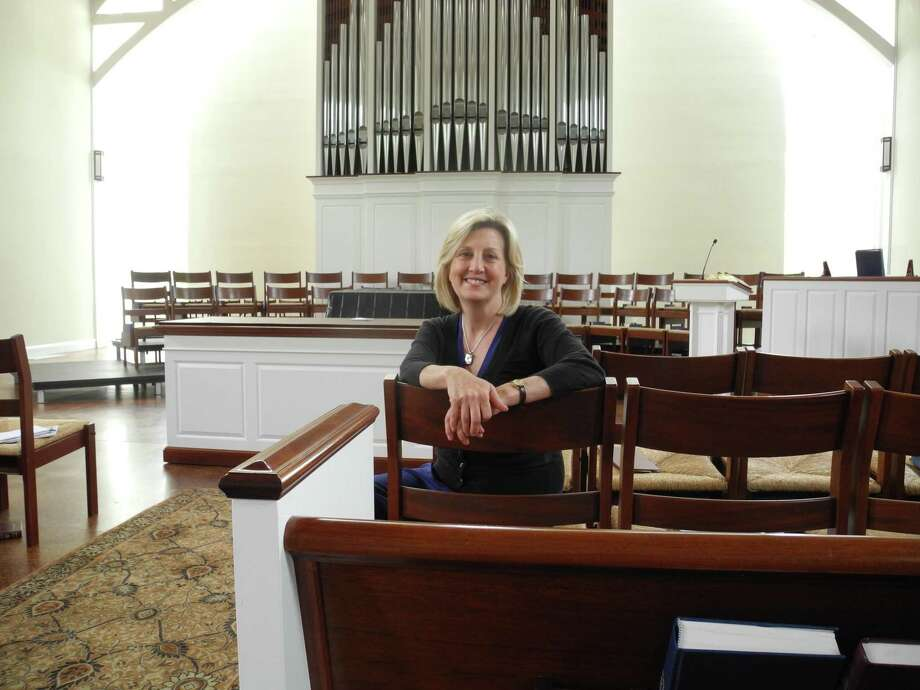 Wilton Presbyterian Pastor the Rev. Shannon White sits in the church sanctuary. She said parishioners have been greeting one another with elbow bumps and the distribution of Holy Communion has changed. Photo: Jeannette Ross / Hearst Connecticut Media / Wilton Bulletin Contributed