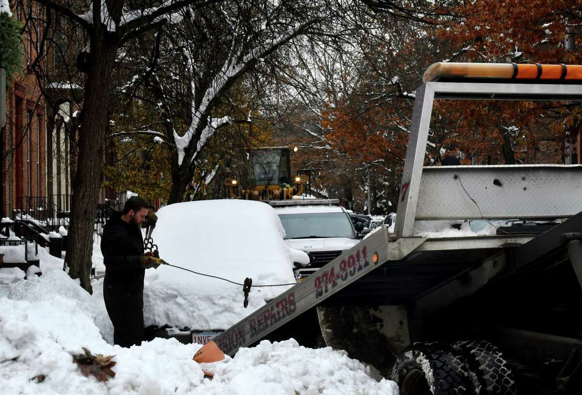 A snow-covered car is towed from Second Street in Troy, as city crews work to clear roads following a major snowstorm on Wednesday, Dec. 4, 2019, in Troy, N.Y. (Will Waldron/Times Union)