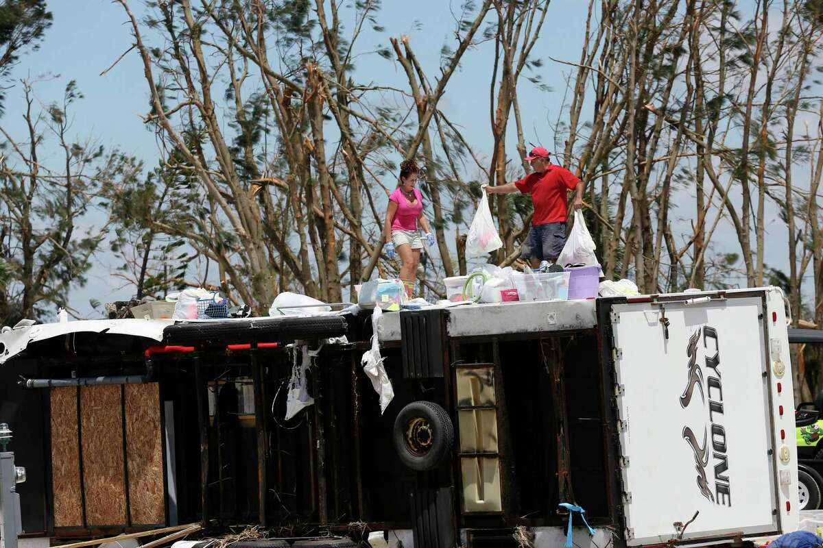 Glen Gonzales, 47, helps Brenda Travieso, 53, both from San Antonio, remove personal belongings from a travel trailer in the Tropic Island Resort in Port Aransas, Texas. The trailer and many others in the area were damaged by the surge and wind from Hurricane Harvey last Friday night.