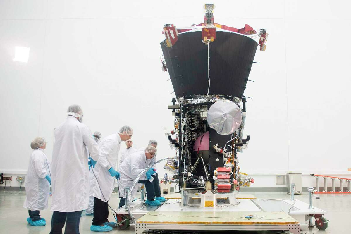 (FILES) In this file photo taken on March 28, 2018 Engineers examine the Parker Solar Probe during a media preview at NASA Goddard Space Flight Center in Greenbelt, Maryland. - Car sized and protected by a very thick heat shield, NASA's Parker Solar Probe probe travels closer to the Sun than any spacecraft in history. Four studies are published today in