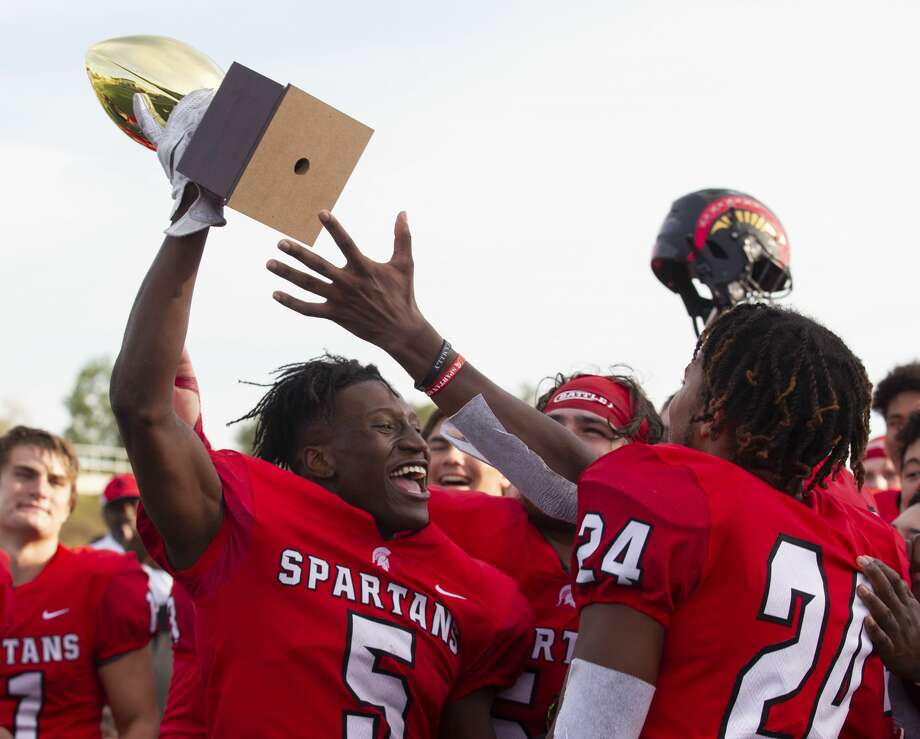 Porter wide receiver Jojo Guillory (5) holds up a trophy after the Spartans defeated Hightower 21-17 during a Region III-5A bi-district high school football playoff game at Randall Reed Stadium, Saturday, Nov. 16, 2019, in New Caney. Photo: Jason Fochtman/Staff Photographer