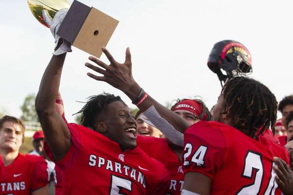 Porter wide receiver Jojo Guillory (5) holds up a trophy after the Spartans defeated Hightower 21-17 during a Region III-5A bi-district high school football playoff game at Randall Reed Stadium, Saturday, Nov. 16, 2019, in New Caney.