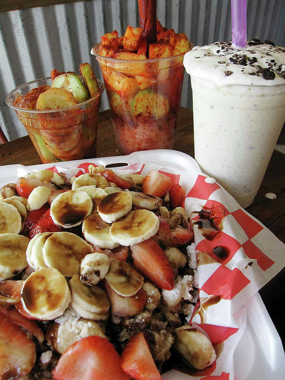 Snacks and desserts include a build-your-own funnel cake (bananas, strawberries and chocolate syrup), a cucumber cup, a Shack Fruit Cup with fruit and chamoy shaved ice and an Oreo shake at The Shack.