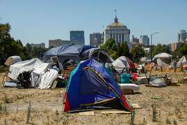 Tents are seen at an encampment on East 12th Street in Oakland, California, on Wednesday, July 24, 2019. Ollie and his partner Debbie are currently homeless. They went through Oakland's Tuff Shed program where they resided before getting permanent housing in Stockton. After spending a month in an apartment in Stockton the couple moved back to an encampment in Oakland because they claimed the apartment was infested with rats and cockroaches.