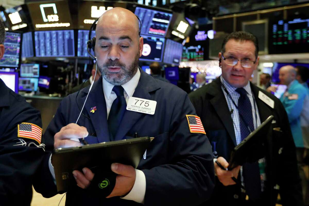 Traders Fred DeMarco, left, and Edward Curran work on the floor of the New York Stock Exchange, Wednesday, Dec. 4, 2019. Stocks are opening broadly higher as traders became more hopeful that a trade deal between the U.S. and China was making progress. (AP Photo/Richard Drew)