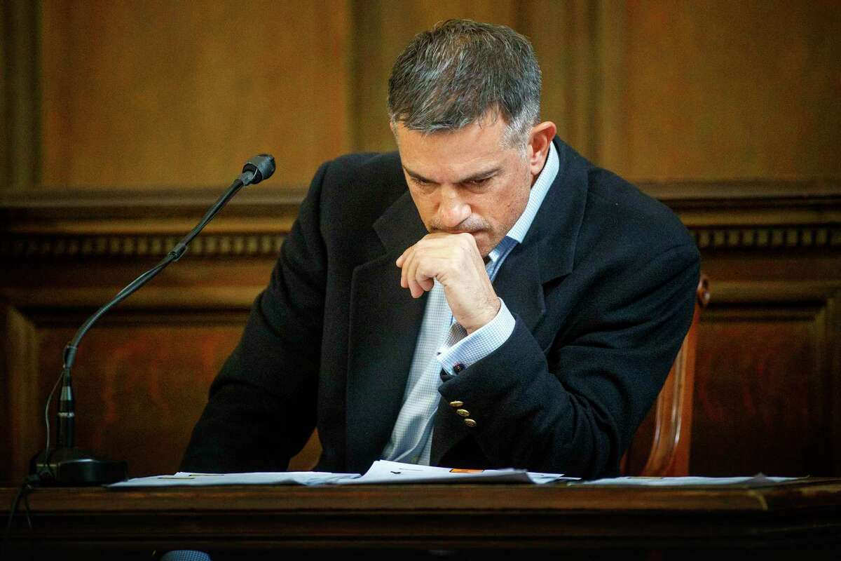 Fotis Dulos examines a financial document presented by his attorney William Murray during testimony in a civil case in Hartford Superior Court during his testimony in a civil case Wednesday, Dec. 4, 2019, in Hartford, Conn.
