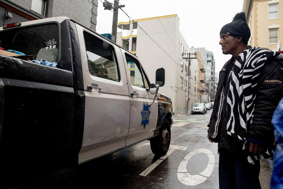 Rico (no last name given) watches as a SFPD truck drives down Willow Street with a bed full of homeless residents' belongings during a sweep of homeless tents and encampments by the Department of Public Works and San Francisco Police along Willow Street in San Francisco, Calif. Wednesday, Dec. 4, 2019.