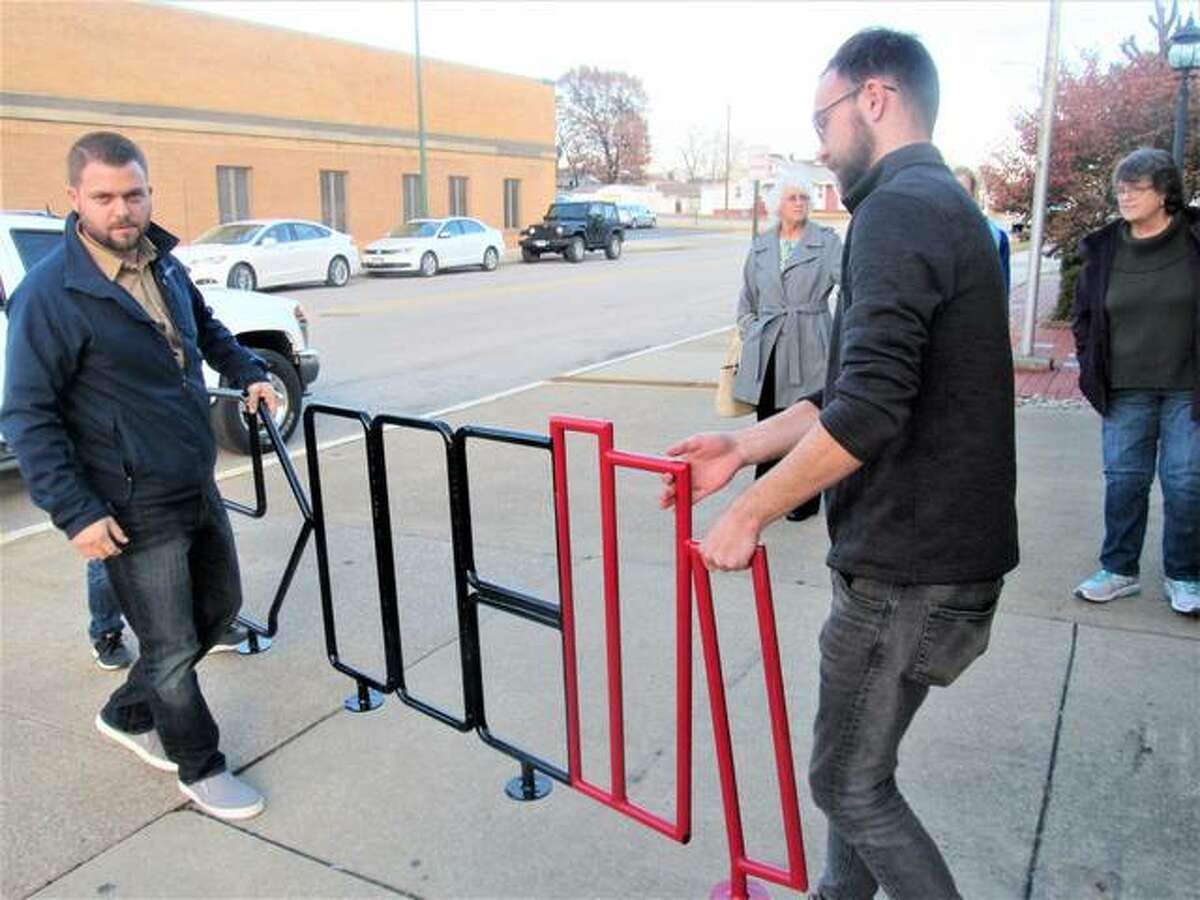 Wood River Library Foundation member Andy Russell and Stock Auto Body and Mechanical employee Dylan Eberhart transfer a new bike rack to the Wood River Public Library.