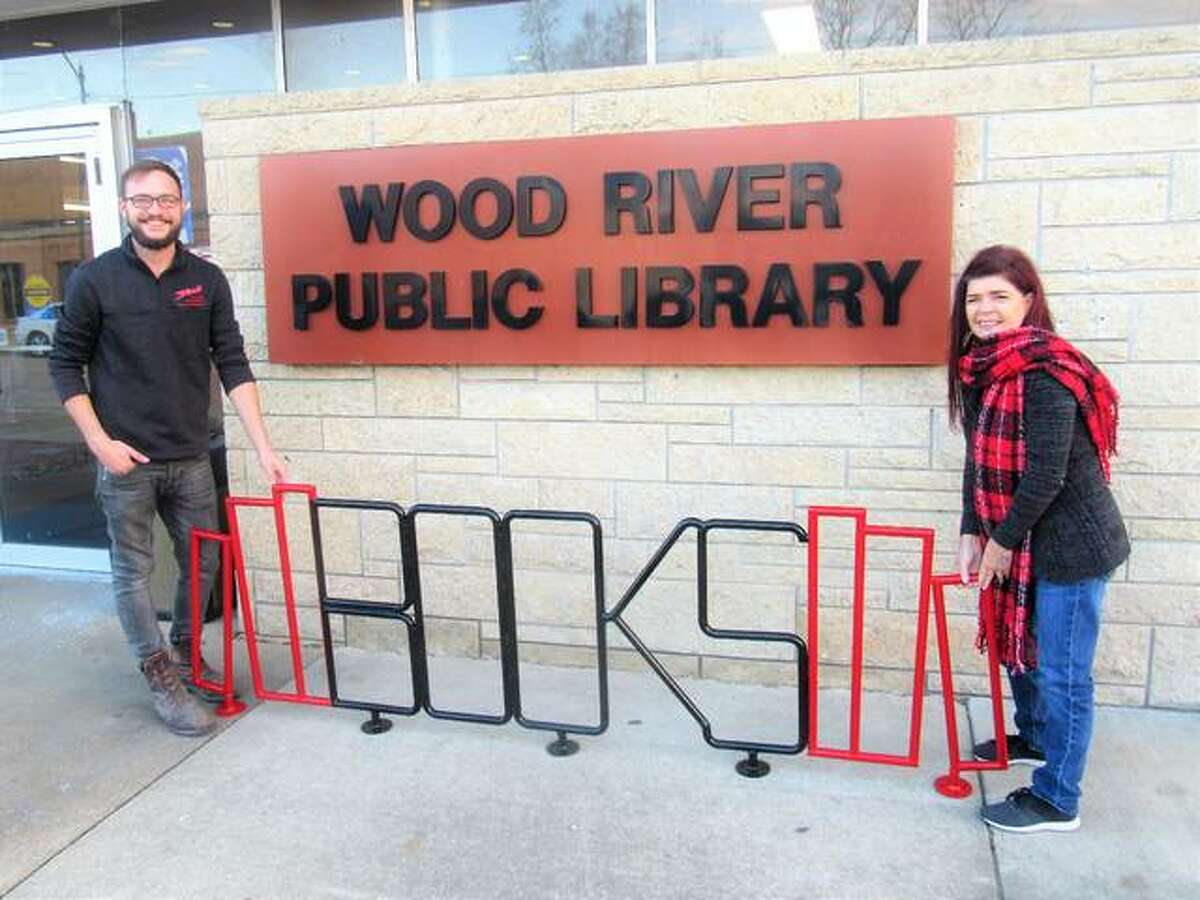 Eberhart, with Stock Auto Body and Mechanical, and his mother pose with the new bike rack at Wood River Public Library. The bike rack was the last project owner Kent Eberhart approved before he passed away in late October.